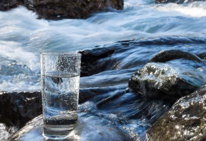 Natural water in a glass next to a river